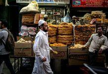Pedestrians walk past stalls selling food outside the Jama Masjid | Sanjit Das | Bloomberg