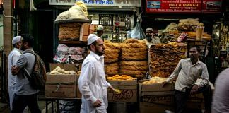 Pedestrians walk past stalls selling food outside the Jama Masjid | Sanjit Das | Bloomberg