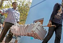 Poll workers carry EVMs at a distribution centre