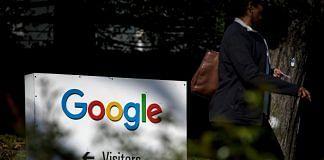 A pedestrian walks past signage at Google Inc. headquarters in Mountain View, California, U.S. | Photo: David Paul Morris