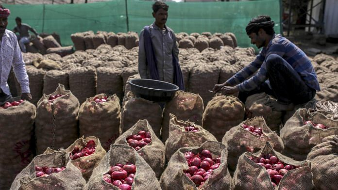 A worker sews up a sack full of onions