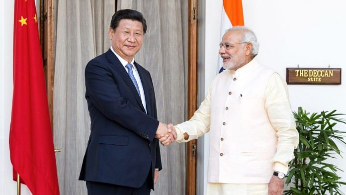 Narendra Modi shakes hands with Xi Jinping, China's president | Photo: Graham Crouch | Bloomberg