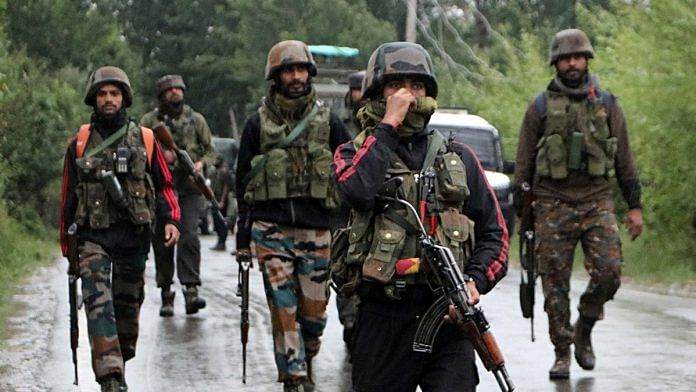 Army personnel take position after an IED blast in Pulwama
