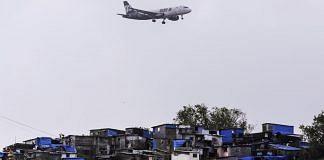 A plane flies over Mumbai slums | Dhiraj Singh/Bloomberg