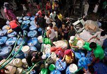 Residents fill empty vessels for drinking from a Delhi Jal Board tanker in New Delhi