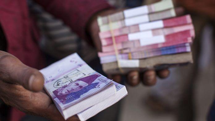 A roadside money changer handles bundles of Pakistani rupee banknotes at a currency exchange market in Pakistan. | Photographer: Asim Hafeez | Bloomberg