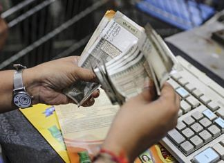 A cashier counts Indian rupee bank notes. | Photographer: Dhiraj Singh | Bloomberg
