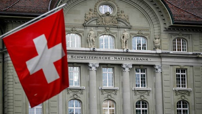 A Swiss national flag hangs in view of the Swiss National Bank (SNB) in Bern, Switzerland