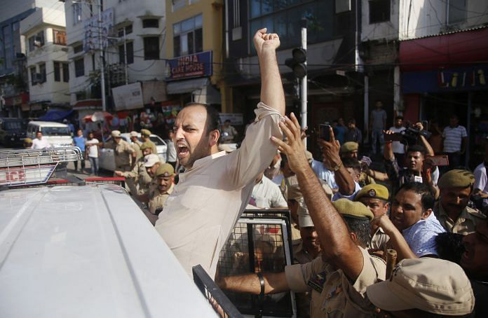 Jammu & Kashmir police detain a member of Youth Congress during a protest
