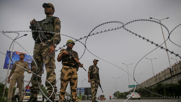 Paramilitary personnel stand guard during restrictions in Jammu