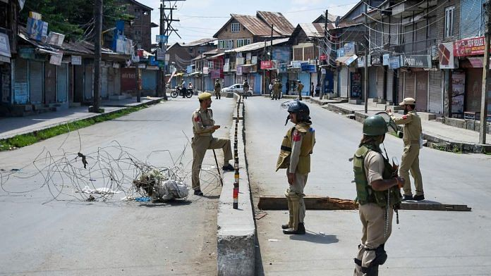 Security personnel stand guard at a check point during restrictions in Sringar