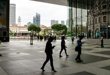 Pedestrians walk in front of the office buildings in the central business district in Singapore. | Photo: Sanjit Das | Bloomberg