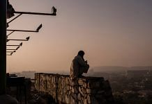 A man is silhouetted as he sits on a wall at the top of Bibi Mahru Hill in Kabul