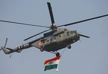 An Indian Air Force military helicopter displays an Indian flag as it flies past during the Republic Day Parade | Bloomberg