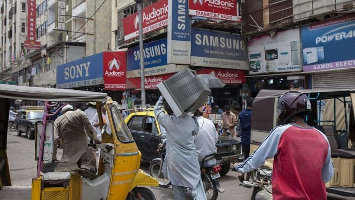 A man carries television set on his shoulder, while walk past an electronic market in Karachi, Pakistan(representational image) | Photographer: Asim Hafeez | Bloomberg