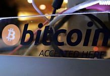 "A sign reading ""Bitcoin Accepted Here"" is displayed next to a cash register at The Pink Cow restaurant and bar in Tokyo, Japan. 