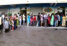 Voters stand in a queue displaying their voter card outside a polling station during Maharashtra Assembly elections in Thane | PTI