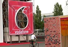 A cyclist rides passed a Vodafone Group Plc logo at the company's exhibition space during the CeBIT 2018 tech fair in Hanover, Germany. | Photographer: Kriztian Bocsi | Bloomberg