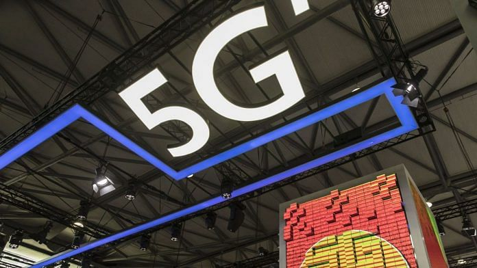 Visitors walks past a large 5G display at a China Unicom booth at the Mobile World Congress in Shanghai