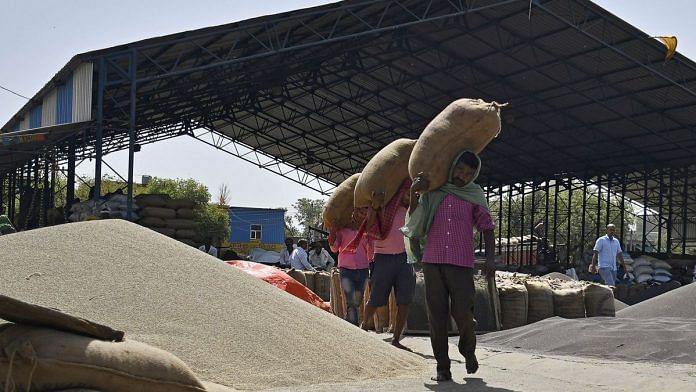 Workers load sack of Barley onto a truck at a grain market in Rewari, Haryana. | Photographer - Anindito Mukherjee | Bloomberg