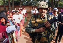 A security jawan keeps vigil as people wait in queues to cast their votes at a polling station during the first phase of Jharkhand Assembly elections. | PTI
