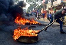 A demonstrator burns tyres on National Highway 17 during a protest rally against CAB, at Boko in Kamrup district of Assam