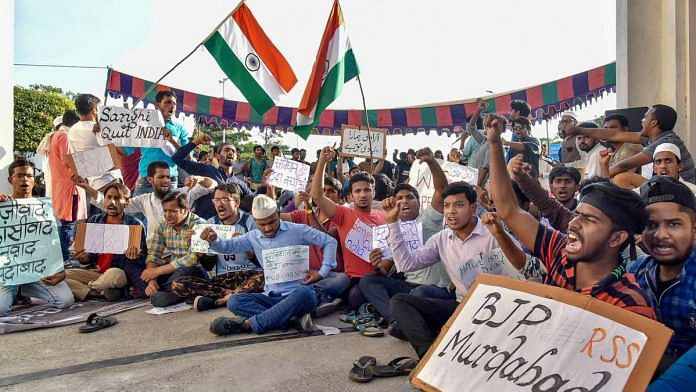 Maulana Azad National Urdu University students hold placards during a protest in front of the university entrance against Citizenship (Amendment) Act (CAA) and NRC, in Hyderabad,