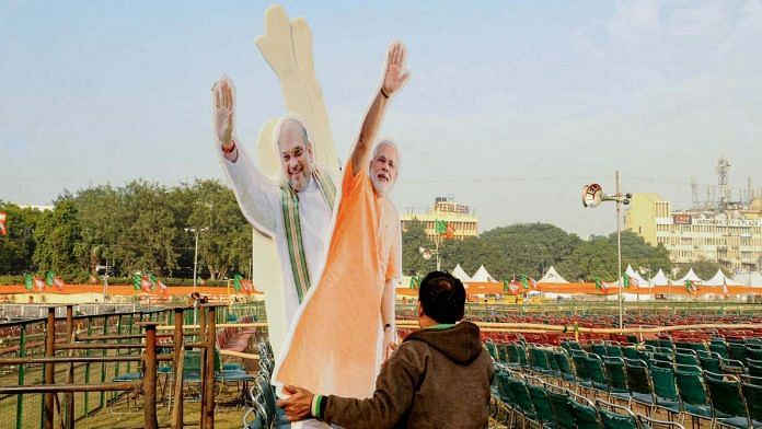 A workers carries cut-outs of Prime Minister Narendra Modi and Union Home Minister Amit Shah at Ramlila Maidan in New Delhi on 21 December