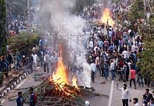 Protestors burn hoardings during their protest strike against Citizenship Amendment Bill in Guwahati