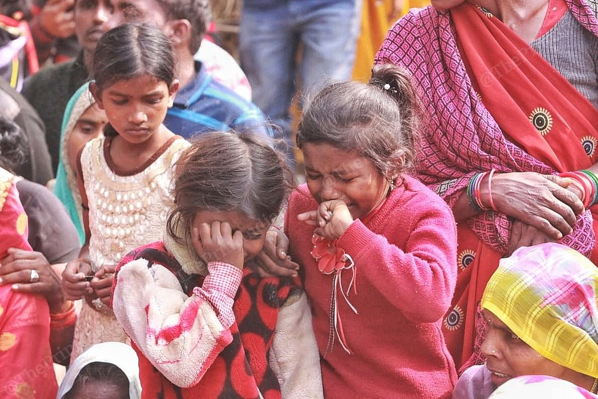 Two young children crying inconsolably at the burial of the victim