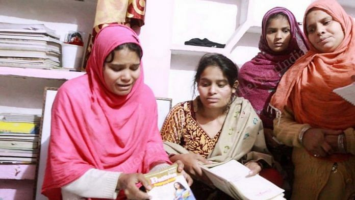 Family members of Suleiman, who was killed in violence in UP's Bijnor Friday, show the books he was using to prepare for the UPSC exam | Photo: Praveen Jain | ThePrint