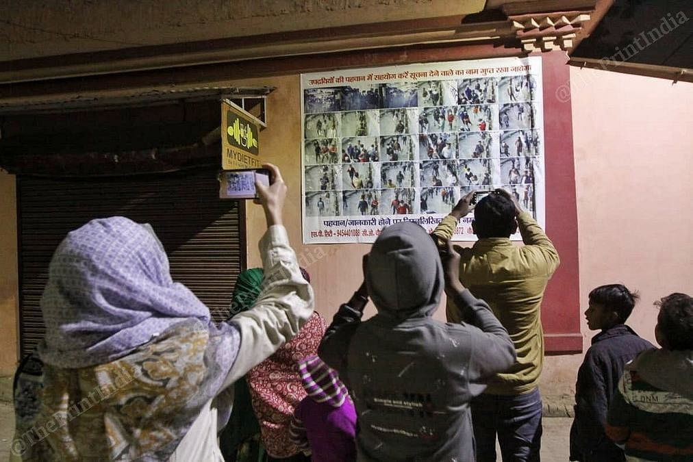 Residents observing and clicking pictures of a 'wanted' banner in Lucknow's Hussainabad. | Photo: Praveen Jain/ThePrint