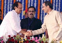 Maharashtra chief minister Uddhav Thackeray shakes hand with NCP leader and deputy CM Ajit Pawar during the swearing-in ceremony in Mumbai.   Photo: ANI
