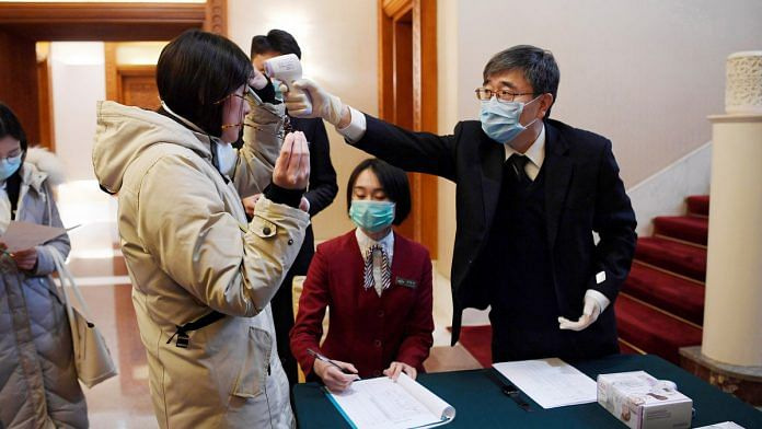 A man uses a thermometer to check the temperature of a journalist covering a meeting between Tedros Adhanom, director-general of the World Health Organization, and Chinese Foreign Minister Wang Yi in Beijing on Tuesday | ANI/Reuters