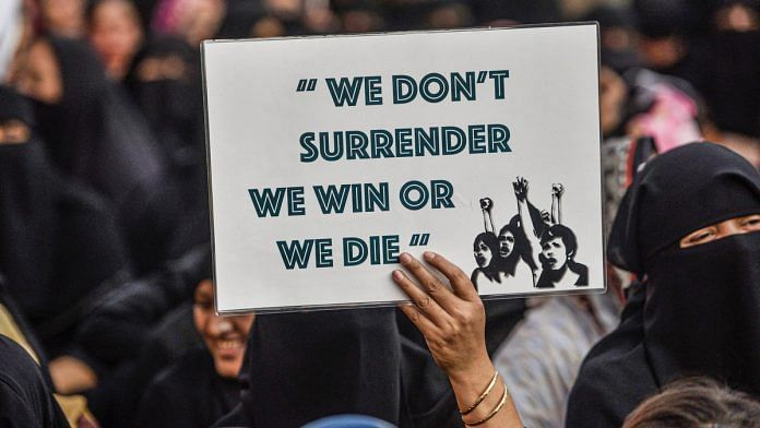 A protestor holds a placard during a demonstration against CAA and NRC in Mumbai