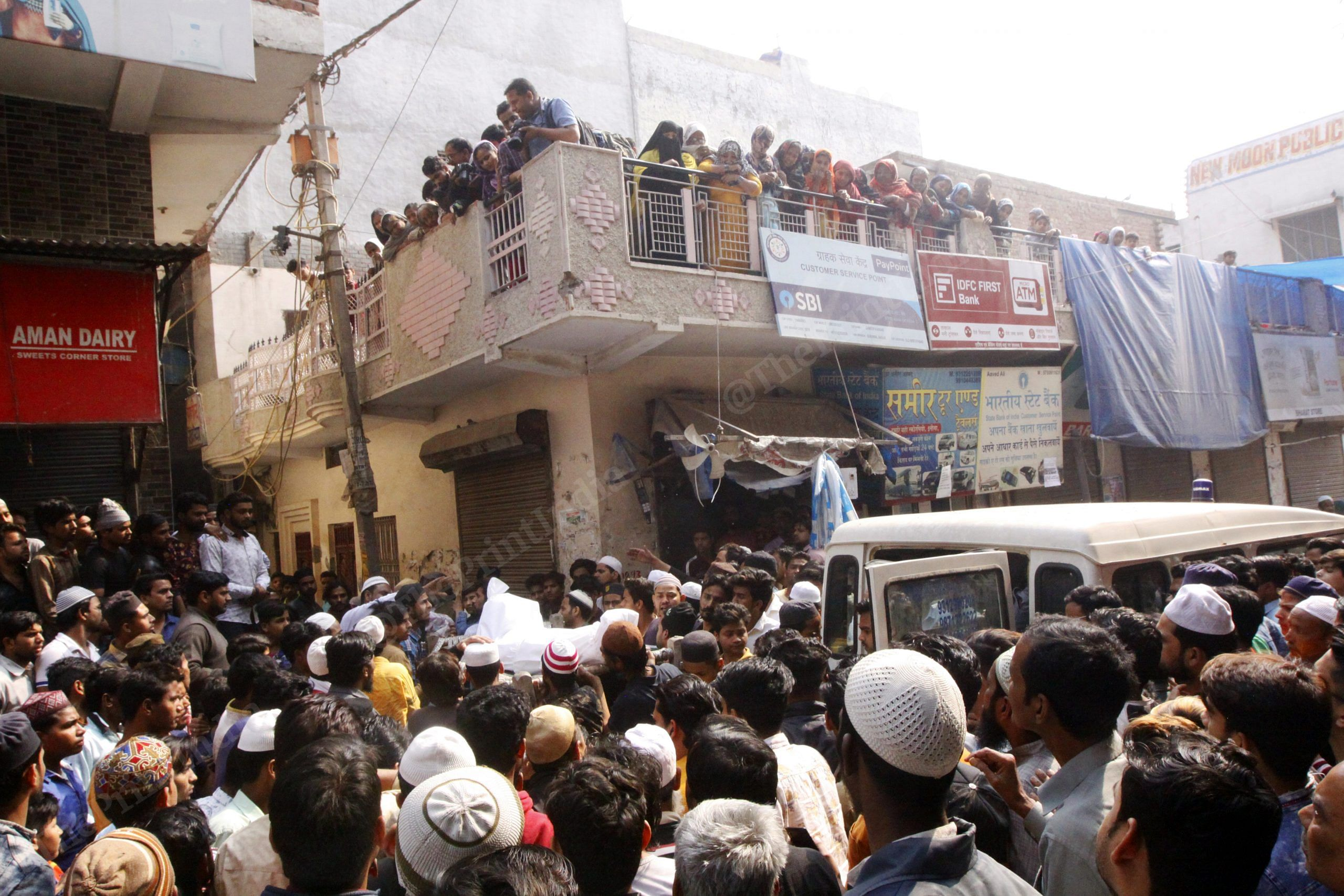 As the bodies reach their residence, hundreds gather to take them out from the van. Bodies being escorted to their residence inside a narrow bylane | Photo: Praveen Jain | ThePrint