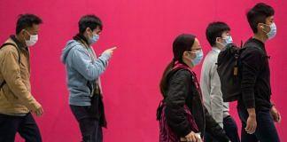 People wearing masks walk at Central district in Hong Kong, China | Paul Yeung/Bloomberg