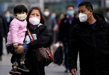 Passengers wearing masks walk outside the Shanghai railway station in Shanghai, China