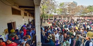 Voters wait in queues at the Abul Kalam Azad school polling station in Shaheen Bagh