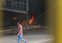 A man walks by a fire burning at a walkway in Northeast Delhi's Gokulpuri on 25 February 2020   Manisha Mondal   ThePrint