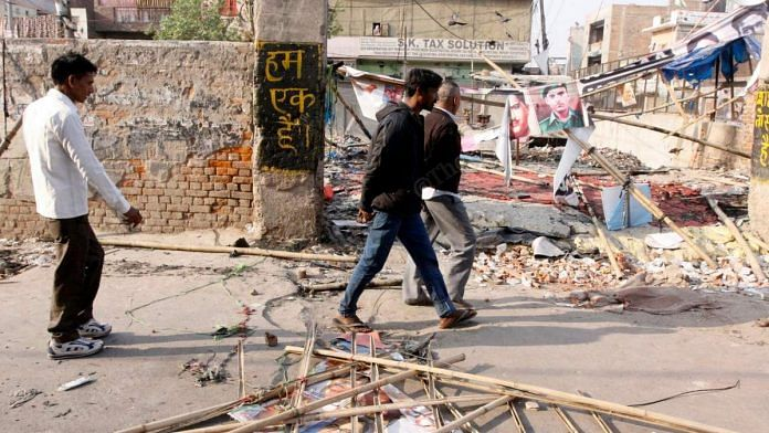 People walk by a sign reading 'hum ek hain' (we are one) in riot-hit Mustafabad in Northeast Delhi | Photo: Praveen Jain | ThePrint