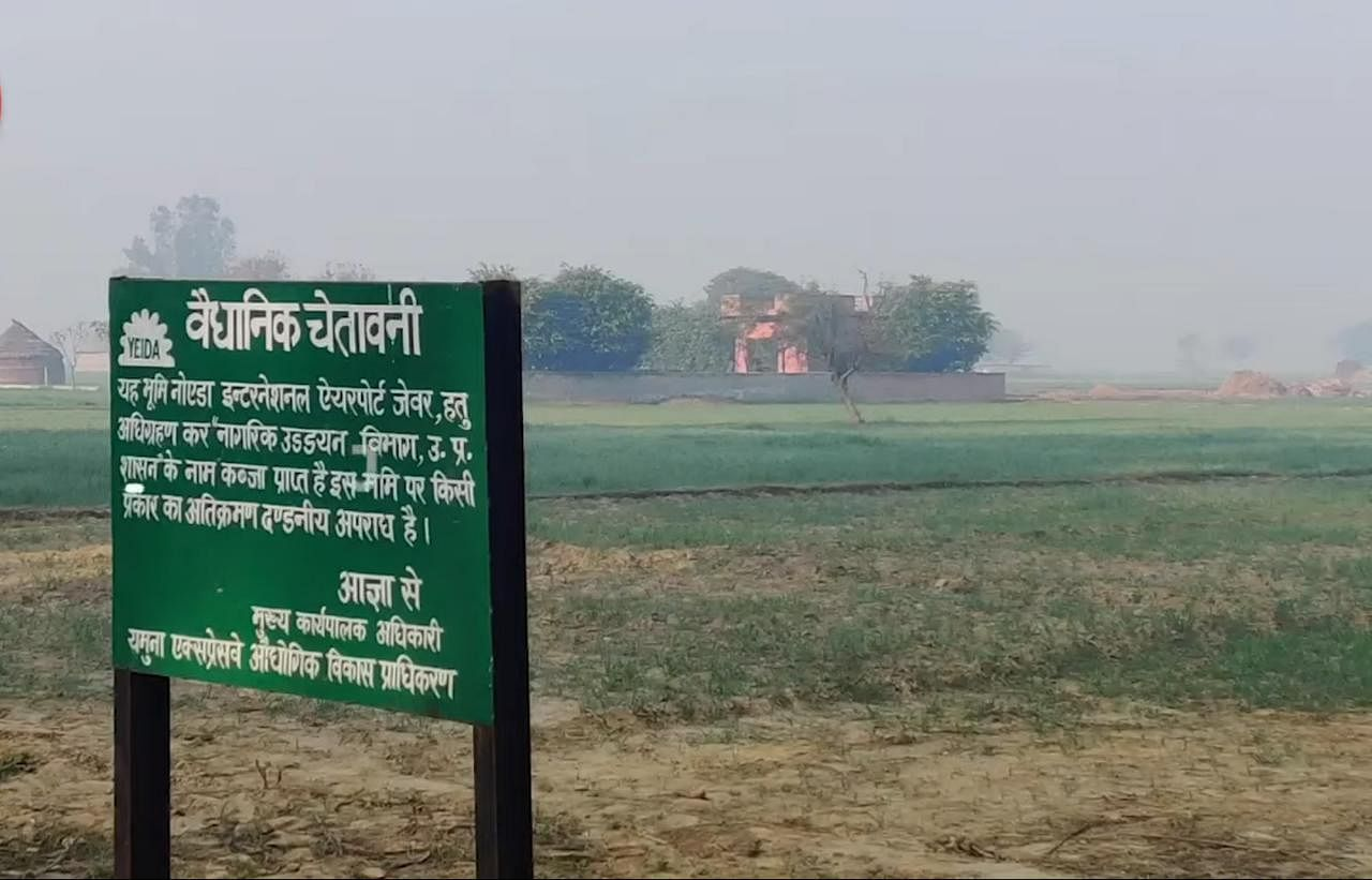 A signpost declaring the land acquisition for the Noida International Airport in Jewar   Photo: Unnati Sharma   ThePrint
