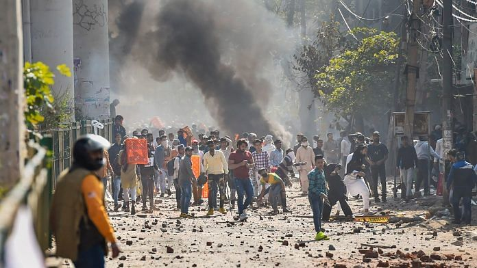 Protestors throw brick-bats during clashes between a group of anti-CAA protestors and supporters of the new citizenship act, at Jafrabad in north-east Delhi | PTI