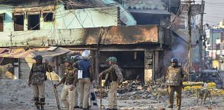 Security personnel stand guard near a neighbourhood vandalised by rioters during clashes between those against and those supporting the Citizenship (Amendment) Act in north east Delhi, Tuesday, Feb. 25, 2020. | PTI