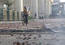 A man cycles past an empty road in Gokulpuri, Delhi, which saw arson and violence during communal riots that broke out in February 2020 | Manisha Mondal | ThePrint File Photo