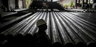 A worker stands in front of steel tubes at the Steel Authority of India Ltd in Rourkela, Odisha | Dhiraj Singh | Bloomberg File photo
