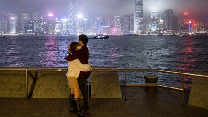 People wearing protective masks embrace while standing against the city skyline at night in the Tsim Sha Tsui district of Hong Kong | Justin Chin/Bloomberg
