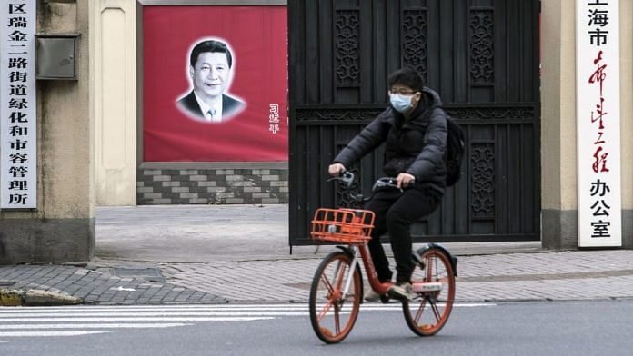 A cyclist wearing a protective mask rides past a banner of Chinese president Xi Jinping in Shanghai   Qilai Shen/Bloomberg