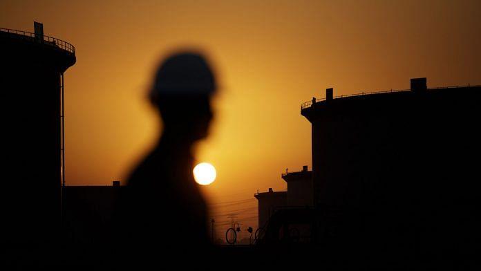 The sun sets beyond crude oil storage tanks at the Juaymah tank farm at Saudi Aramco's Ras Tanura oil refinery and oil terminal in Ras Tanura, Saudi Arabia, on Monday, Oct. 1, 2018. | Photographer: Simon Dawson | Bloomberg