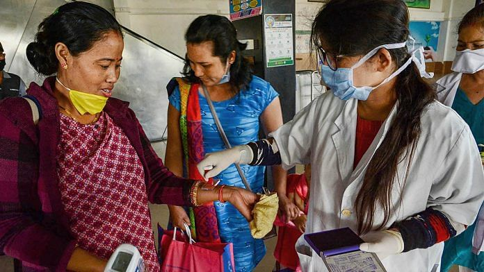 Medics place home quarantine stamps after thermal screening at Guwahati Railway station in wake of the coronavirus pandemic | PTI